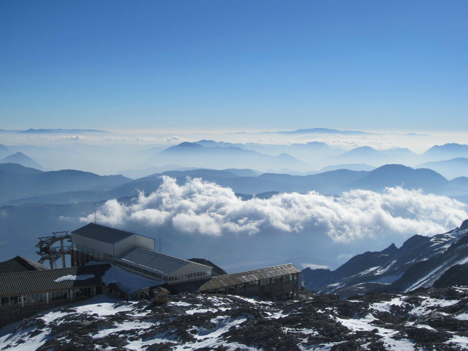 如果说彩云之南的丽江是连接天堂与人间最便捷的通道之一的话,那么玉龙雪山则是通道里的门关了。作为纳西族人民膜拜的雪山,视为一种神圣而不可侵犯、不可征服的神山。其实,这并非言过其实。倘若你到达玉龙雪山很远的位置看这座雪山,初步的感觉就是很美丽、很壮观。由于丽江的海拔很高、玉龙雪山很高很远,视角很广泛。所以从距离50公里之外的丽江古城都能够清晰的见到玉龙雪山的倩影。如果是第一次看到高原雪山的话,肯定会激动、兴奋而狂热的去向雪山方向奔跑,并到达雪山零距离的山脚下感受一下玉龙雪山的壮观美景。实际上,通过山野君亲身的