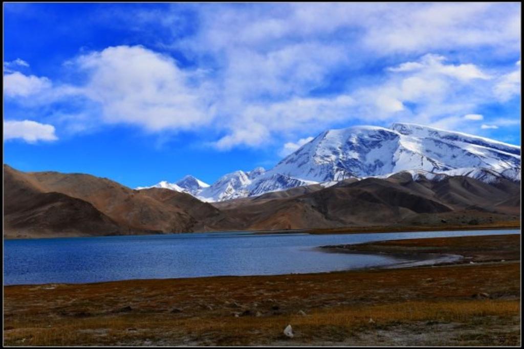 慕士塔格峰,位于阿克陶县与塔什库尔干塔吉克自治县交界处,海拔7509米。地处塔里木盆地西部边缘,东帕米尔高原东南部,周边慕士塔格峰、公格尔峰及公格尔九别峰,三山耸立,如同擎天玉柱,屹立在美丽的帕米尔高原上,成为帕米尔高原的标志和代表。 山峰西边坡势平缓,北边和东边却十分险峻。山体浑圆,状似馒头,常年积雪,雪线约海拔5200米,冰山地貌发育十余条冰川,其中最大的栖力冰川和克麻土勒冰川将山体横切为两半,冰川末端到达海拔4300米。山顶冰层厚100-200米,有冰川之父之称。在维语中:慕士为冰的意思,塔