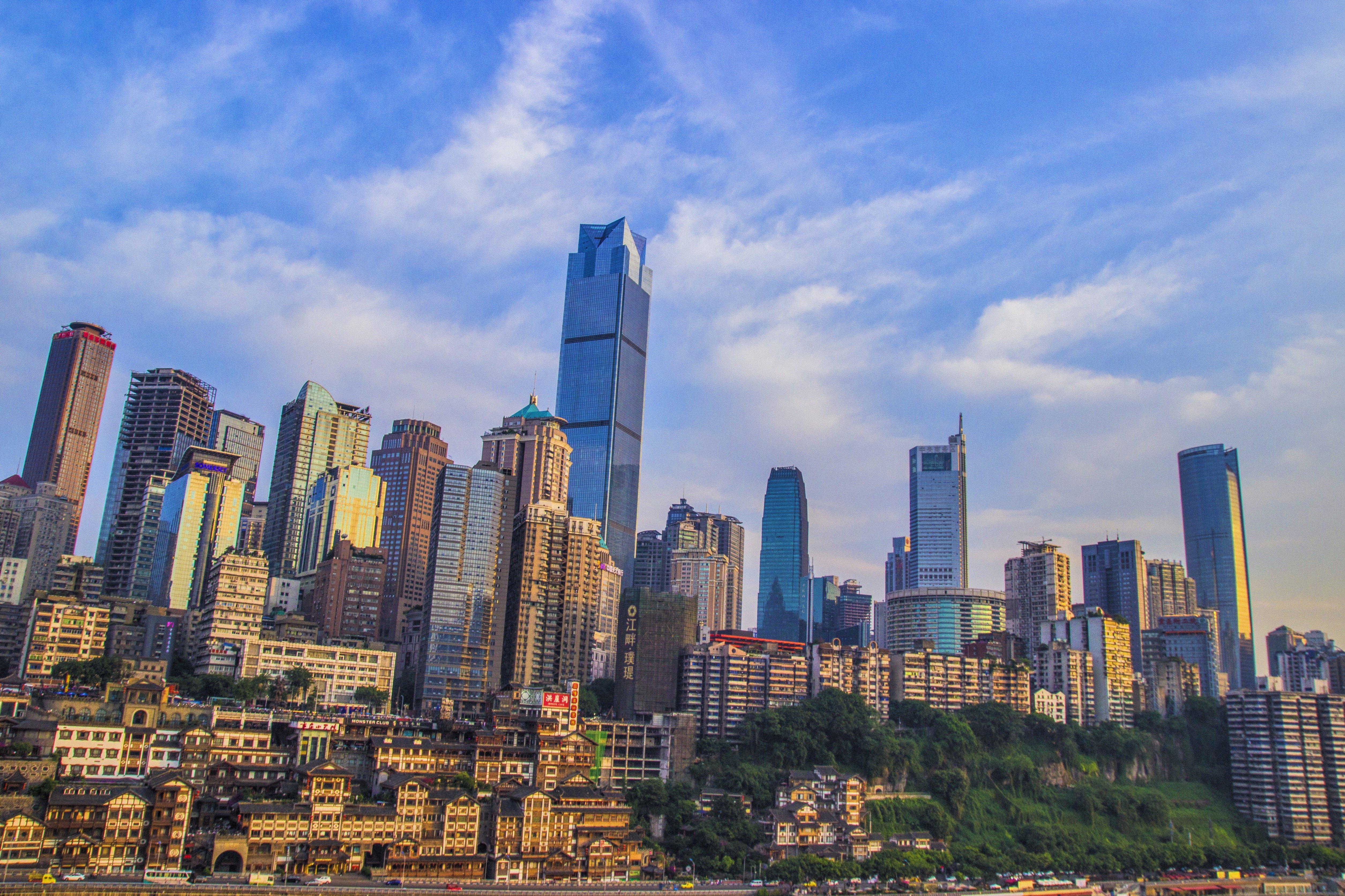 他是以重庆的高楼大厦作为背景,然后自身又是木制结构,差异性很大,看