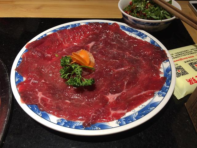 招牌嫩牛肉,把牛肉放在沸腾的火锅中大概15秒左右即可,沾上特制的涮料