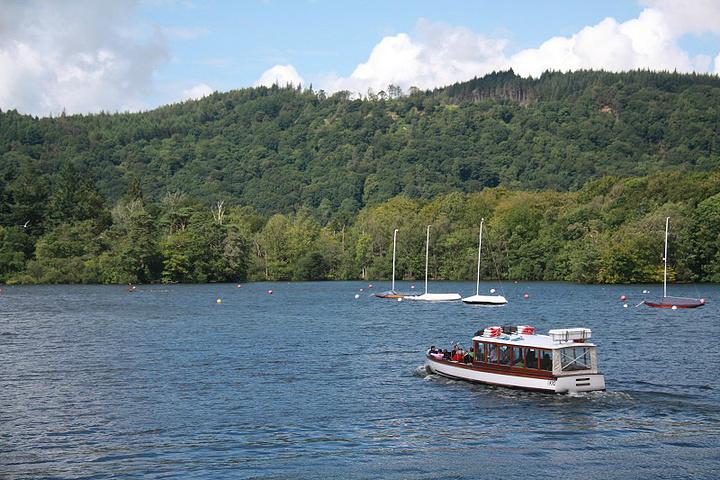 湖边就是草地和山地,湖水平静,湛蓝的天空飘着朵朵棉絮般的白云,夏天
