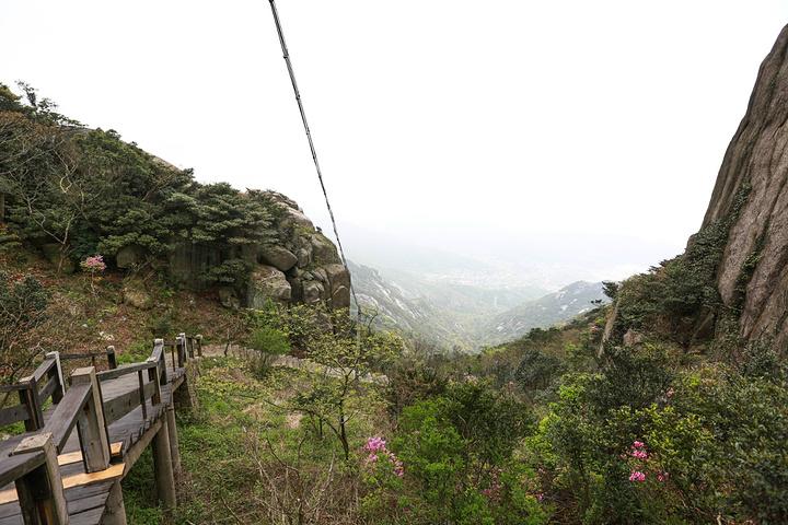 奇峰高耸、风景如画的安期峰景区 这个景区以峰、石为特色,寺、洞为主体。峰就是安期峰,海拔540米,舟山千岛第一高峰。石就是石阵,遍山的奇岩怪石,组成一个白家朝圣大景观,浩浩荡荡,朝着普渡众生的观音石前进。寺就是圣岩寺,位于海拔460米山岙处,是舟山千岛位置最高的寺院。洞就是安期炼丹洞,位于海拔482米高处的一个天然岩洞,是先秦隐士安期生修道炼丹之所。这峰、石、四、洞都是舟山独一无二的。这个景区具有山青、水曲、石趣、峰奇、境幽、气爽的特点,是桃花岛女龙旅游专线必经之路。
