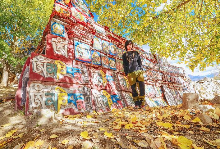 """10月7日,我拜訪拉薩三大寺之一的哲蚌寺。 瓦藍天空下,幾株金燦燦的楊樹,將光影打在一堵完全由繪上彩色佛像的石板石片壘成的石經墻上。 遇上這漂亮光影的場景,我覺得能出好照片,于是自拍。 我引起了一個一身牛仔的藏家青年的注意。 我說我以攝影為業,來藏區已久,這幾天卻不知能去哪里拍些好風景。 青年名叫格日扎西,掏出手機,打開相冊,問我:""""這是我家鄉,你看這里風景怎么樣?"""" 我翻看著,幾座雪山下,一個湖泊中碎裂著多塊冰川。 我自詡博學,這地方卻從未見過,只能向他請教。 格日扎西道:&ld"""