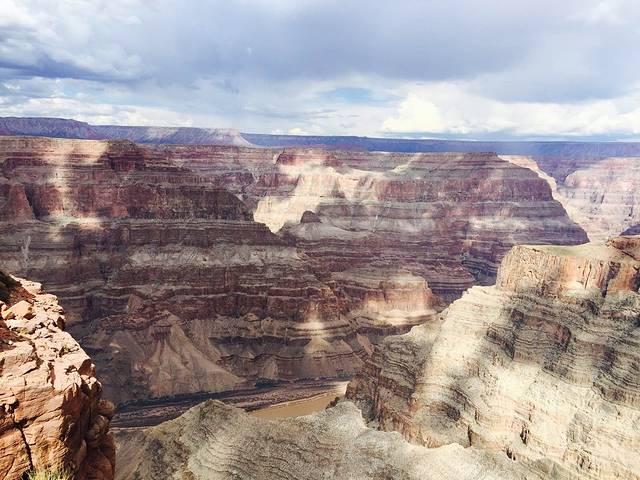大峡谷我们是定的一日游,正好在促销,价格比较实惠,还包含了玻璃桥。因为我们这边有老人有小孩,所以只选择了巴士游,有班车在市区酒店接送,挺方便的。 去大峡谷的途中,一些景色已经很赞了,沙漠的氛围很明显。到了大峡谷之后,领取了各自的标签(套在手上的纸环,坐景区内的巴士及吃饭时需要扫描),就开始了自由活动。巴士游一共是三个景点,巴士下车的地点就是上车的地点: 第一个是体验西部牛仔生活,有牛仔们生活的场景再现,还有打枪游戏玩。第二个景点是老鹰岩,岩石自然成为展翅的老鹰形状,真的挺逼真的,大家纷纷和老鹰合影留念(合