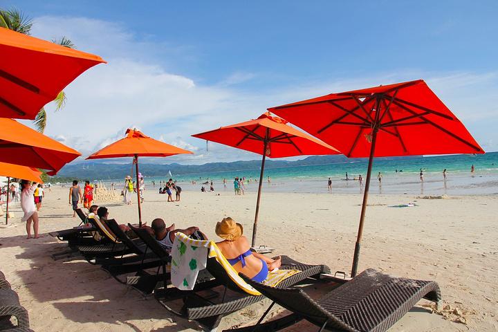 在树荫下吹着海风看美景~ 很多外国人都在晒日光浴,美黑ing~~ ps:阳伞