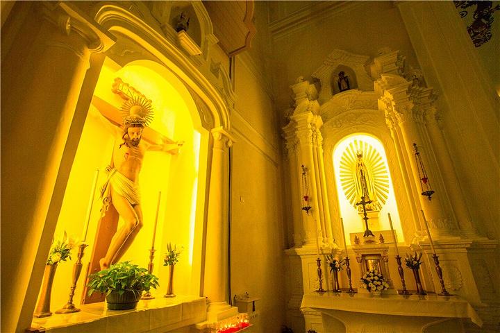 巴洛克风格的祭台上矗立着乳白色的童贞圣母和圣子像.