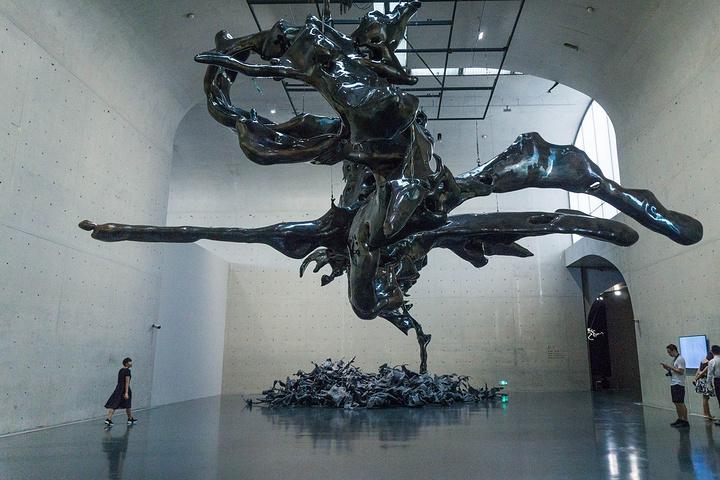 当代艺术品_整墙的当代艺术展品和占据整个空间的巨大抽象金属雕塑震撼着在场的众