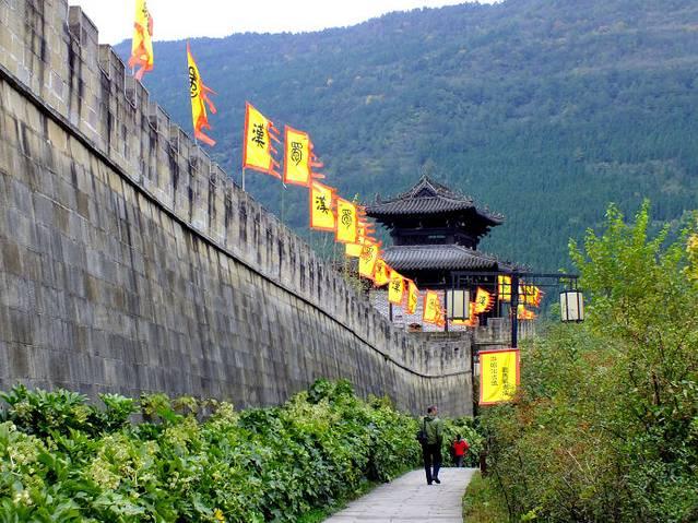 昭化,这座有着4000多年历史,素有巴蜀第一县,蜀国第二都之美誉的古城,不仅与一代女皇武则天渊源深厚,而且还是一个集三国文化、民俗文化和山水文化于一体的风水宝地。虽然已经是春末夏初季节,但地处川北的昭化依然还是清凉山风透着丝丝寒意。古城景区道路两侧整整齐齐插着黄色旌旗,大大的漢字赫然在目,旌旗猎猎,浓浓的三国文化氛围迎面扑来。  昭化的夜如山风一样清凉。虽然才晚上8点多钟,但在古城里游荡的人已不见几个,许多商家都已经关门。古城标志性的物件红灯笼只在街的一边亮着,街道一边红亮温暖,一边黑暗冷清