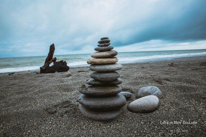 海滩上有各种石头和树枝搭成的抽象作品.