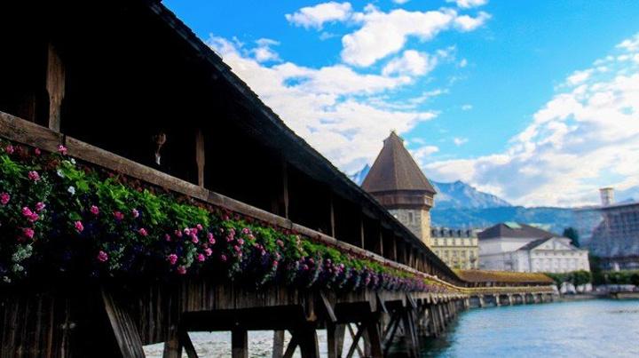 从火车站走到旅馆的路上被风景美呆了的我,完全抛开了自己的疲惫,迅速换了衣服准备出去走走。7月底卢塞恩的天气十分舒服,阳光很暖,也有风,不会太热。晚上的时候会起风,渐渐有些凉,加上一件外套便觉得可以在这样的天气里生活一辈子。 卢塞恩有名的卡佩尔廊桥( Kapellbrücke),从桥的这边可以看到远处绵延的山和蓝得发光的水,还有沿着水复古的欧式建筑。卢塞恩唯一的缺点就是游客很多,卡佩尔廊桥附近都挤满了游客。他们被一辆辆旅游大巴拉来,四散在街头的免税商店里,嘈杂的声音和这自带静音的美景有些格格不入。