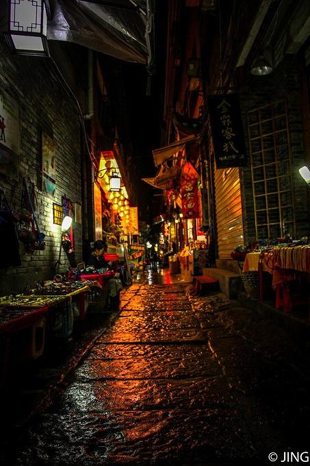 傍晚又下起了小雨,昏暗的灯光照射之下古城的石板路显得特别漂亮.