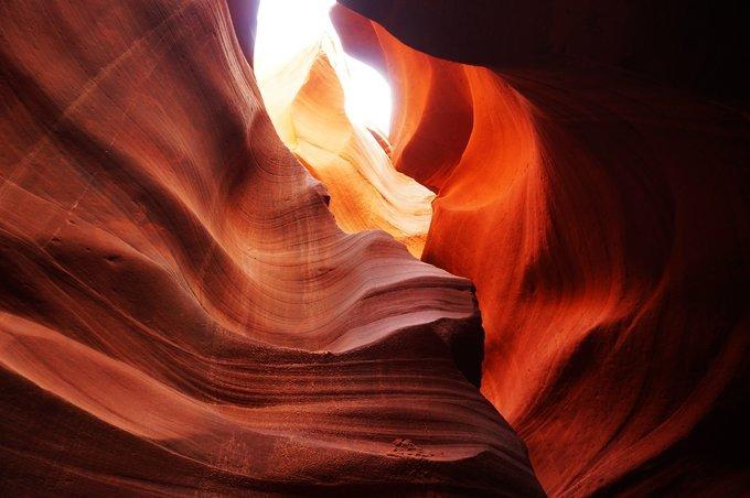 射幼谷_谷壁如海浪般起伏 红色的砂岩,随着岩壁方向曲折回旋,配上峡谷顶部射