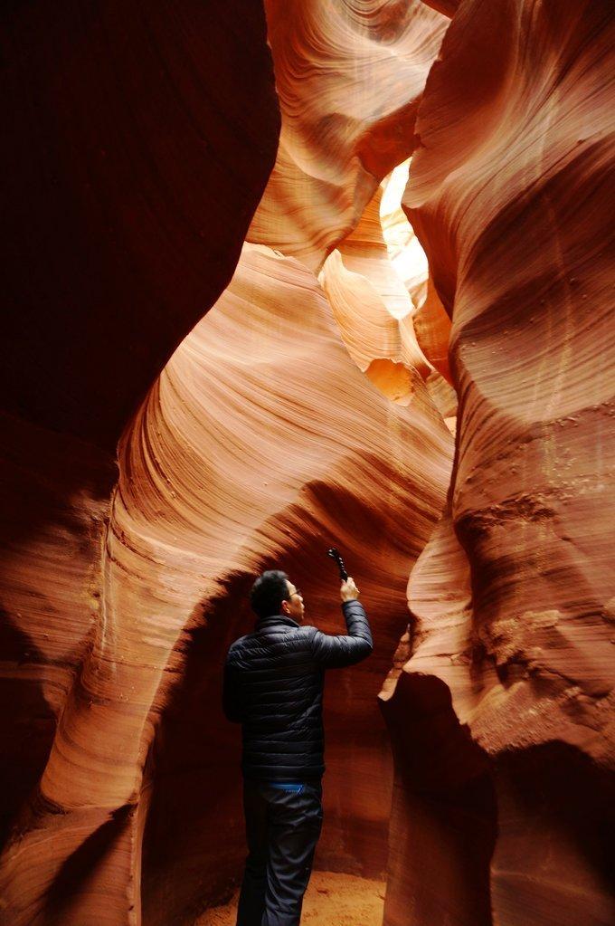 射幼谷_红色的砂岩,随着岩壁方向曲折回旋,配上峡谷顶部射进的光线,岩壁从