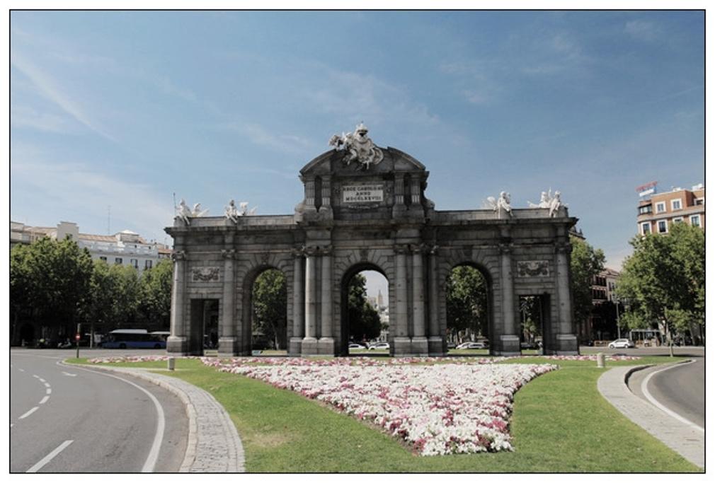 广场一侧的阿尔卡拉大道通往阿尔卡拉门,马德里现存的几座最古老的城门之一。1769年西班牙国王卡洛斯三世在比较了文图拉•罗德里格斯和萨巴蒂尼的几套设计方案后,决定任命萨巴蒂尼在此兴建一座宏伟的新城门,以取代原本位于附近的一座十六世纪老城门。这座新古典主义风格的新城门于1778年落成,采用大型罗马凯旋门的形式。它也是整个欧洲自古罗马帝国衰落后兴建的第一座凯旋门,早于1791年建成的勃兰登堡凯旋.