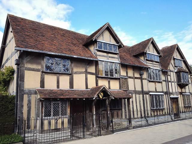 木结构的房屋框架,斜坡瓦顶,泥土原色的外墙,凸出墙外的窗户和门廓使