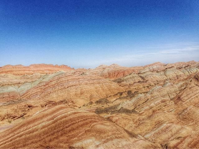 敦煌雅丹国家地质公园,俗称敦煌雅丹魔鬼城。是敦煌西线旅游大景区的一个重要组成部分,距离敦煌市区180公里,在罗布泊边缘.雅丹地貌是一种典型的风蚀性地貌。雅丹在维吾尔语中的意思是具有陡壁的小山包。现泛指干燥地区一种风蚀地貌,河湖相土状沉积物所形成的地面,经风化作用、间歇性流水冲刷和风蚀作用,形成与盛行风向平行、相间排列的风蚀土墩和风蚀凹地(沟槽)地貌组合。 经过玉门关遗址和汉长城遗址,需要为这两个景区交费40元,雅丹阳光比较强,很晒,门票50,景区内车费70,里边的大巴汽车定时发车,每半小时一班车.