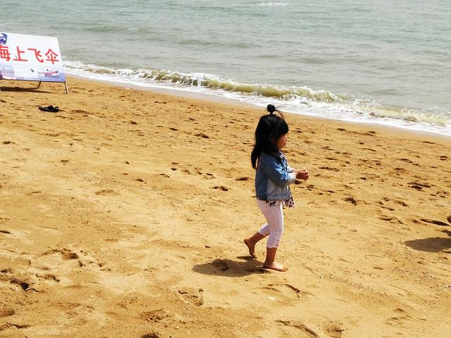 海边不乏可爱宝宝的身影,光着脚丫踩在沙滩上