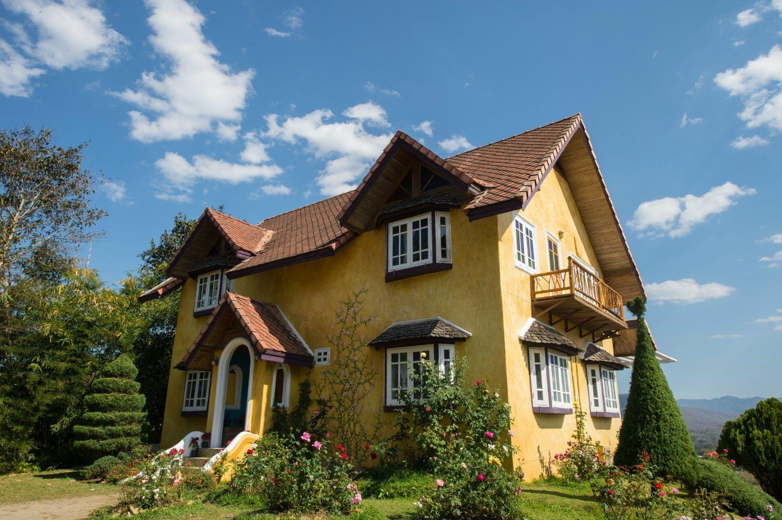 房子的建筑风格是欧式田园风格的,黄色的小屋在蓝天白云的映衬下格外