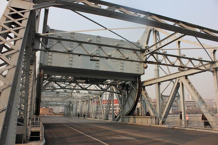 """我们从但丁广场步行到解放桥,它位于世纪钟广场的对面以及天津火车站的侧对面。为了纪念天津解放,在49年后更名为""""解放桥""""。全身钢结构,可开启,所以汽车行驶在桥上都会有""""咯噔""""的声音。"""