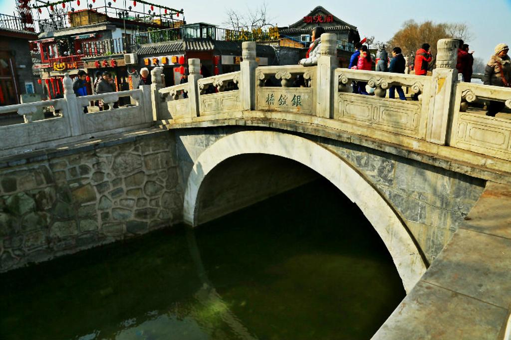 """银锭桥位于什刹海的前海和后海之间,顾名思义,它的外形如银锭一般,故称银锭桥。站在银锭桥上向西望去,可以看见西山,这就是著名的燕京小八景之一——""""银锭观山""""。如今,来来往往的有人穿桥而过,这里的夜晚也被后海的的繁华,渲染的热闹异常,过了银锭桥,绕着后海走一圈,再去荷花市场买些小吃。"""