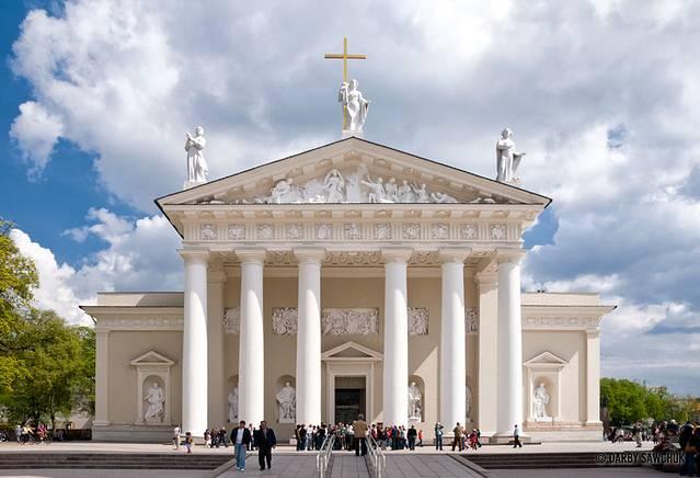 气势恢弘的维尔纽斯大教堂,是这座东欧小城的宗教中心,也是整个城市的标志性建筑。洁白色外观,六根巨大的石柱矗立于正殿之前。教堂的正前方,还矗立着一座高大的白塔,黑色的塔顶之上,一座十字架赫然挺立。 由维尔纽斯老城步行,只需要几分钟,便可以到达教堂广场。维尔纽斯大教堂,便坐落于整座广场的中心区域。这座气势宏伟的大教堂,外观最为引人入胜的,便是正面顶端的三座雕像。中间的圣安娜女神高举着神圣的十字架。左边的圣斯塔尼斯拉夫以及右边的圣卡斯米拉斯相伴,远眺教堂,便可以望见三尊威严的塑像,令人感受到神圣伟大的力量。 这